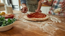 Cropped shot of couple making pizza together at home. Man in apron adding, applying tomato sauce on the dough while woman adding mozzarella cheese. Hobby, lifestyle. Selective focus. Web Banner