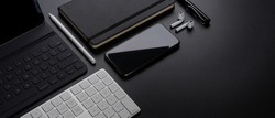 Cropped shot of digital devices with smartphone, tablet, keyboard, stationery, accessories and copy space on dark table