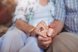 Cropped shot of elderly couple holding hands while sitting together at home. Focus on hands.