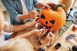 Cropped shot of family parent with little kids preparing for holiday Halloween, hands of mother with children drawing scary face with paint brushes together on pumpkin for house decoration
