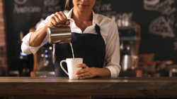 Cropped shot of female barista making a cup of coffee while standing behind cafe counter. Young woman pouring milk into a cup of coffee.