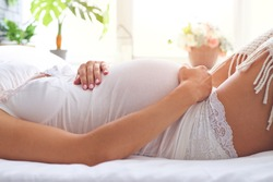 Cropped shot of female hands holding pregnant belly