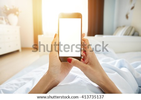 Cropped shot of female holding cell phone with blank copy space screen for your promotional content. Woman using smart phone while lying in bed against home interior background. Film effect, flare sun