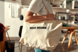 Cropped shot of female worker posing with custom shopper bag in the store. Young woman working at custom T-shirt, clothing printing company. Horizontal shot. Selective focus