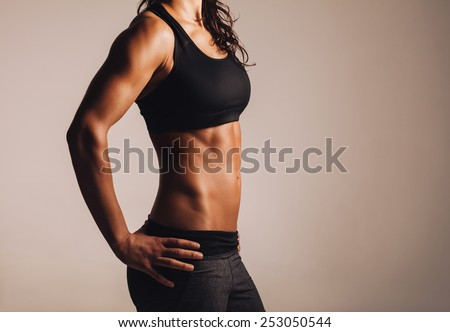 Cropped shot of fit woman\'s torso with her hands on hips. Female with perfect abdomen muscles.