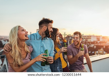 Cropped shot of four friends hanging out on a rooftop