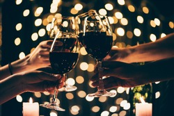 Cropped shot of four people clinking glasses with red wine in front of bokeh background