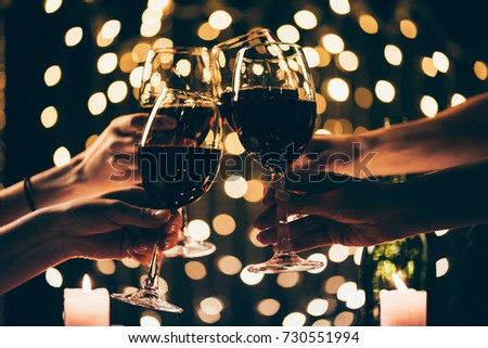 Cropped shot of four people clinking glasses with red wine in front of bokeh background #730551994