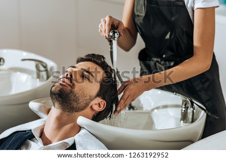 cropped shot of hairstylist washing hair to handsome young man in beauty salon