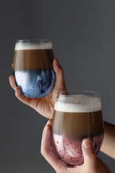 Cropped shot of hands holding two glasses of cocoa. Glasses have blue and pink mirror coating. Glasses full of cocoa with froth. Kitchen items are on the dark gray background.