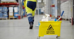 Cropped shot of janitor with bucket washing floor in warehouse focus on yellow cart with industrial worker cleaning floor with mop on storehouse background