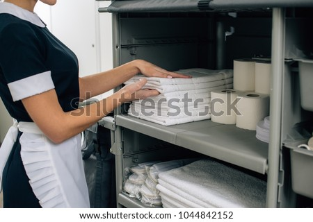 cropped shot of maid in uniform taking towels from shelf of housekeeping cart #1044842152