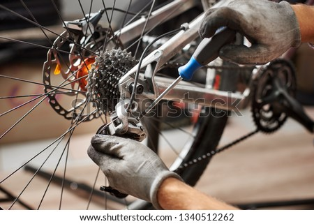 Cropped shot of male mechanic working in bicycle repair shop, mechanic repairing bike using special tool, wearing protective gloves