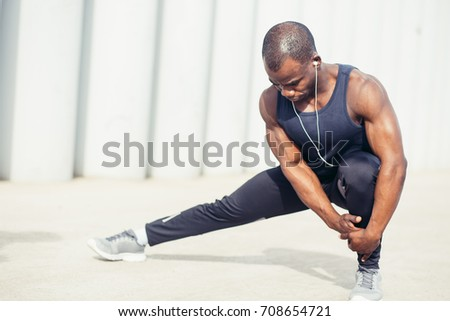 Cropped shot of male runner in black sportswear stretching legs before doing morning workout. Young African jogger warming up before outdoor run, standing on steps of concrete stair, touching toes