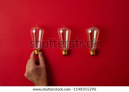cropped shot of man arranging vintage incandescent lamps in row on red tabletop