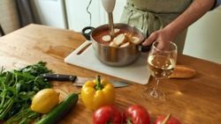 Cropped shot of man, chef cook using hand blender, blending chopped vegetables and bread while preparing Italian meal in the kitchen. Cooking at home, Italian cuisine. Selective focus. Web Banner