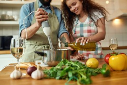 Cropped shot of man, chef cook using hand blender while preparing a meal. Young woman, girlfriend in apron pouring olive oil in the pot, helping him in the kitchen. Cooking at home. Horizontal shot