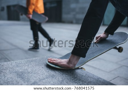 cropped shot of man fixing skateboard with stone wall corner #768041575