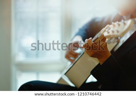 Cropped shot of man playing acoustic guitar. #1210746442