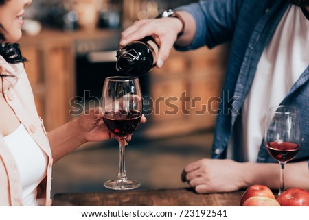 cropped shot of man pouring red wine to woman #723192541