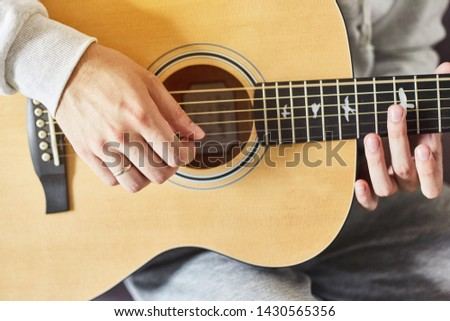 Cropped shot of man practicing in playing acoustic guitar. Close-up of man hand playing guitar. stock photo