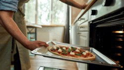 Cropped shot of man, professional cook making pizza at home. Man in apron putting raw pizza in modern oven for baking. Hobby, lifestyle. Selective focus. Side view. Web Banner