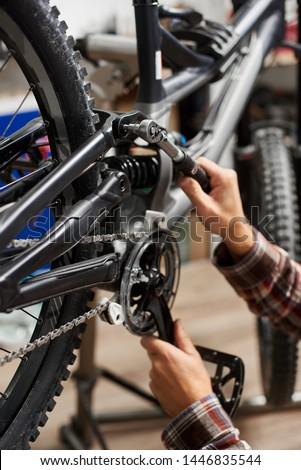 Cropped shot of man repairer working in bicycle repair shop, mechanic repairing modern bike using special tool #1446835544