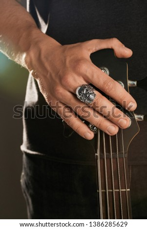 Cropped shot of man's hand, touching headstock of guitar. The guy is wearing signet-ring in the view of a skull. The man is wearing black clothes, posing against the dark background with highlight. Foto stock ©