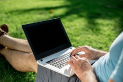 Cropped shot of man using laptop with blank screen while sitting on green grass