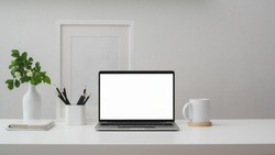 Cropped shot of modern workspace with blank screen laptop, frame, pencils, coffee cup and vase on white table with white wall background