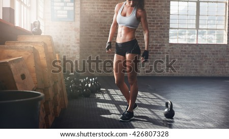 Cropped shot of muscular woman standing in gym. Fitness female model in sportswear with kettle bell on floor.