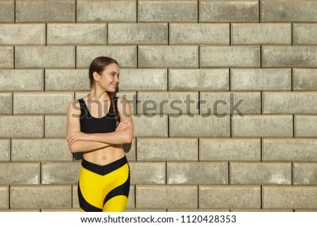 Stock Photo Cropped shot of positive gorgeous young woman wearing trendy black and yellow sports clothes having rest outdoors, posing against blank brick wall background with copy space for your content