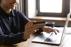 Cropped shot of smiling female sitting before laptop screen holding credit card in hand using e-banking app. Close up of young woman shopping in internet satisfied with easy safe way to pay online