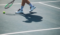 Cropped shot of sportsperson on tennis court. Male tennis player bending on hard court with racket to pick the ball.