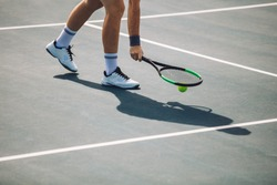 Cropped shot of sportsperson on tennis court picking the ball with racket. Male tennis player pick up the ball on hard court.