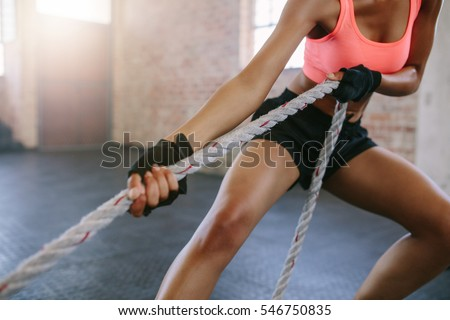 Cropped shot of strong young woman pulling rope at a gym. Female working out with rope at gym.