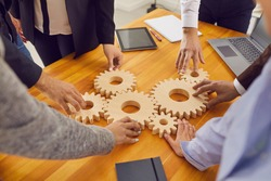 Cropped shot of team of company employees joining cogwheels on office table as metaphor for perfectly working business system, finding best solutions, collaboration, effective teamwork and management
