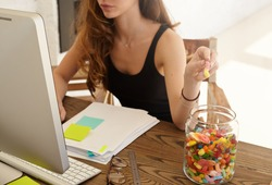 Cropped shot of the Caucasian female office worker taking marmalade from the big jar at work. The girl eats candies for improvement of work of a brain during hard work over the financial statement