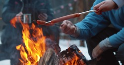 Cropped shot of travelers baking delicious sausages on campfire in winter forest. Group of friends hiking and camping in winter woods and preparing food on fire