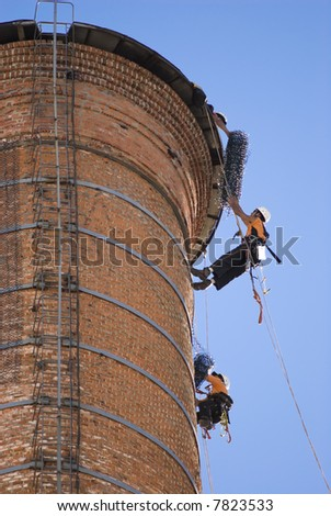 Cropped shot of two unrecognisable workers hanging from a high industrial brick chimney. Blue sky in the background.