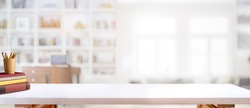 Cropped shot of white table with books, stationery and copy space in blurred study room