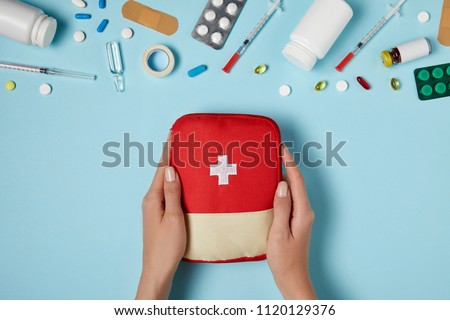 cropped shot of woman holding first aid kit bag over blue surface with various medicines #1120129376
