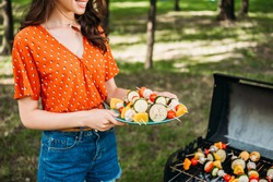cropped shot of woman holding plate with grilled vegetables during barbecue in park