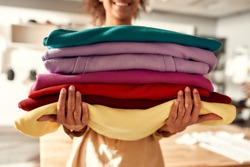 Cropped shot of woman holding stack of colorful sweatshirts, hoodies while standing in the store. Clothes at custom T-shirt, clothing printing company. Horizontal shot