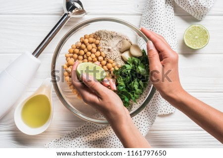 Cropped shot of woman, ingredients for hummus in bowl, olive oil and blender on wooden tabletop