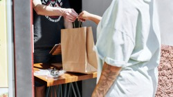 Cropped shot of woman taking paper bag with her order from hands of shop assistant while collecting her purchase from the pickup point. Selective focus. Web Banner