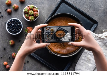 cropped shot of woman taking picture of homemade pie on dark grey tabletop