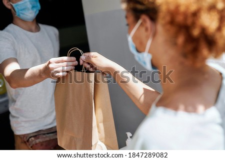 Cropped shot of woman wearing mask taking paper bag with her order from hands of shop assistant while collecting her purchase from the pickup point. Selective focus on hands and bag. Horizontal shot Photo stock ©