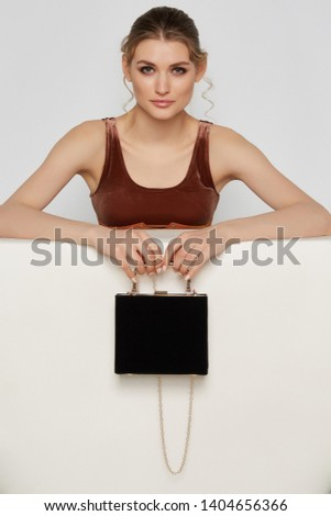 Cropped shot of woman with smokey eyes, wearing bronze velvetine crop top, looking at the camera on gray background. The girl is holding chain strap of ink black box clutch, covered with leather.