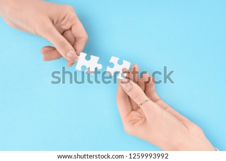 cropped shot of women holding white puzzles in hands on blue backdrop, business cooperation and